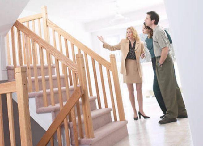Una pareja de extranjeros se inetresa por una vivienda en venta.