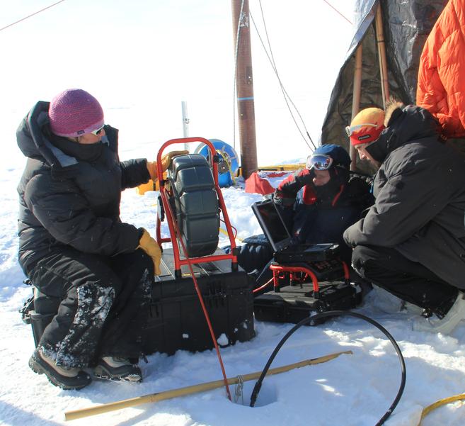 Científicos del proyecto IceBridge introducen una cámara en un...