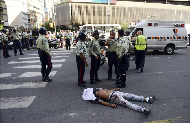 Policías intercambian información frente un hombre asesinado en una...