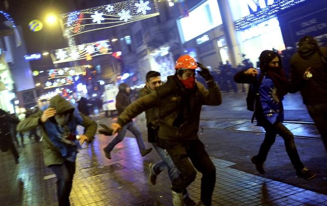 Manifestantes turcos corren a resguardarse de los gases lacrimógenos...