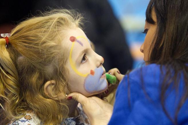 Una monitora pinta el rostro de una niña en ExpoJove.