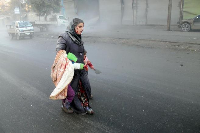 Una mujer herida camina junto a sus hijos por uno de los barrios...