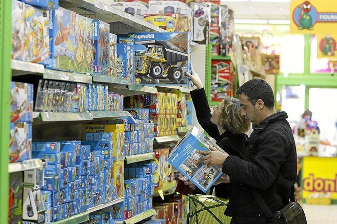 Un hombre y una mujer consultan juguetes en una tienda de Alicante.