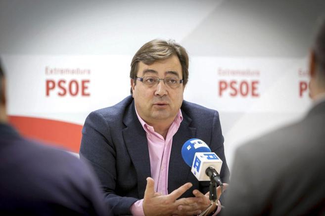 Medio plano de Guillermo Fernández Vara, sentado ante micrófono, a...