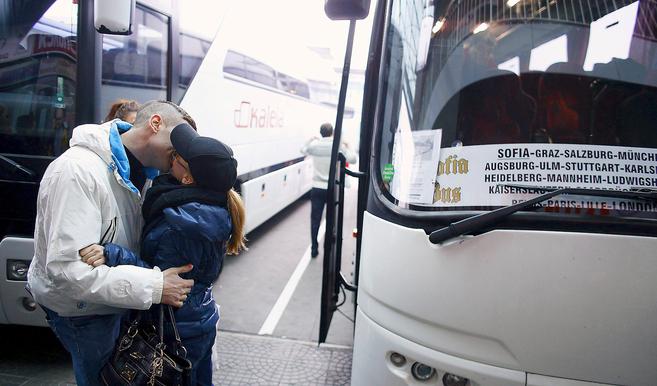 Una pareja se besa en la estación de Sofía junto a un autobús con...