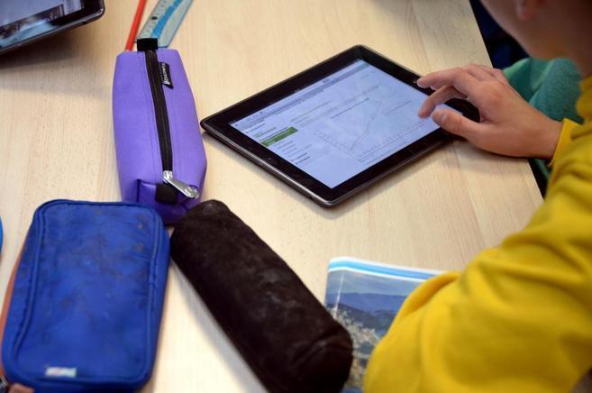 Un niño utiliza una tableta para hacer los deberes escolares.