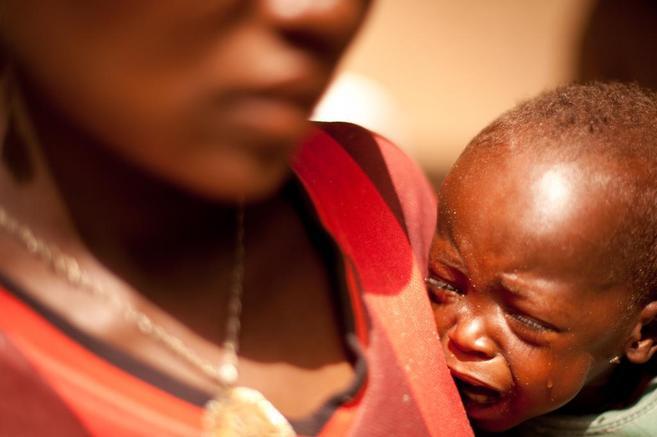 Un niño africano llora en brazos de su madre
