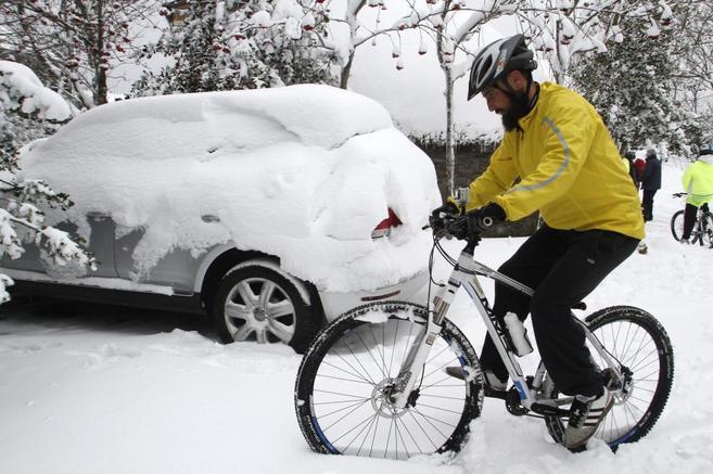 Un hombre intenta avanzar con su bicicleta sobre la nevada caída en O...