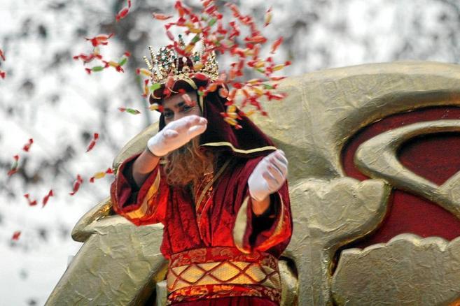 El Rey Melchor lanza caramelos desde su carroza durante la Cabalgata...