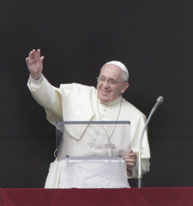 El Papa saluda desde el balcón de la Basílica vaticana.