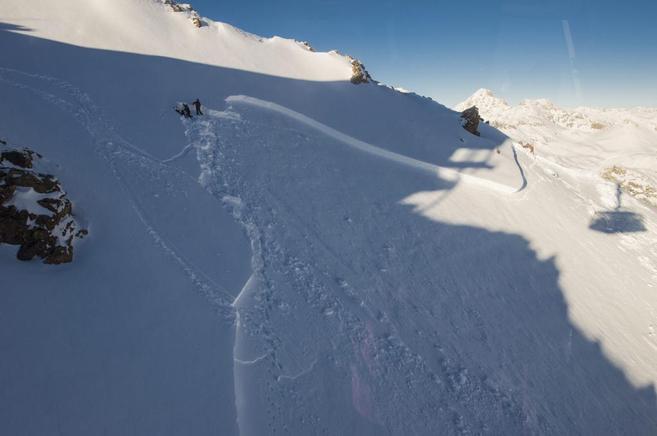 Dos personas inspeccionando una zona donde tuvo lugar una avalancha...