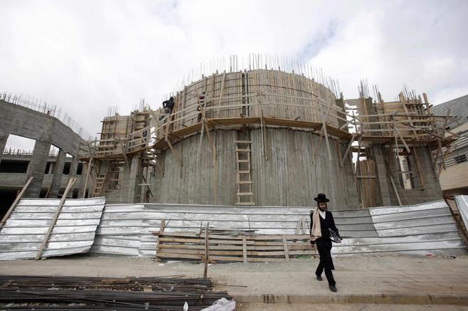 Trabajadores palestinos levantan una sinagoga en un asentamiento...