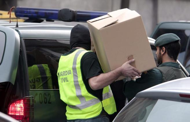 Dos agentes de la Guardia Civil se llevan una gran caja y la están...