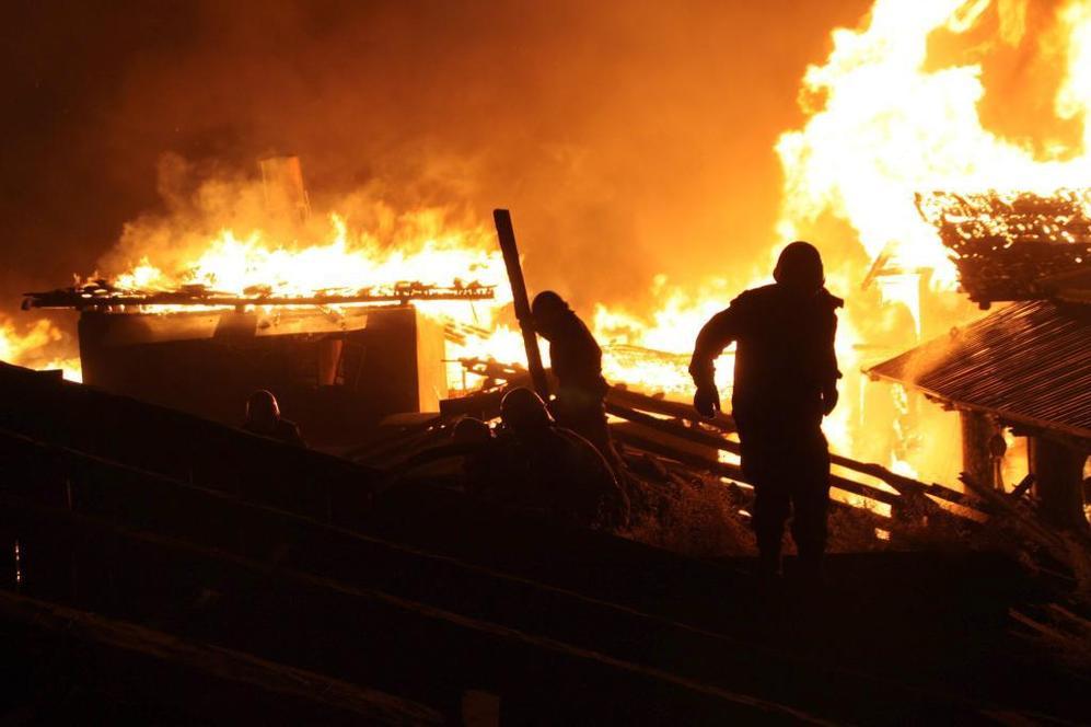 Varias personas tratan de sofocar las llamas.