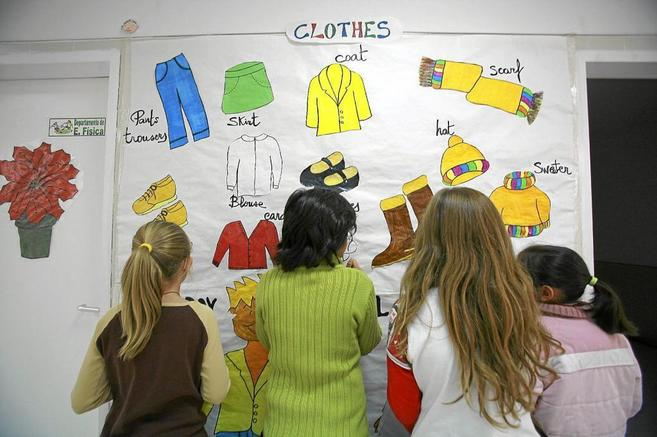 Un grupo de niños aprenden jugando en nombre inglés de prendas de...