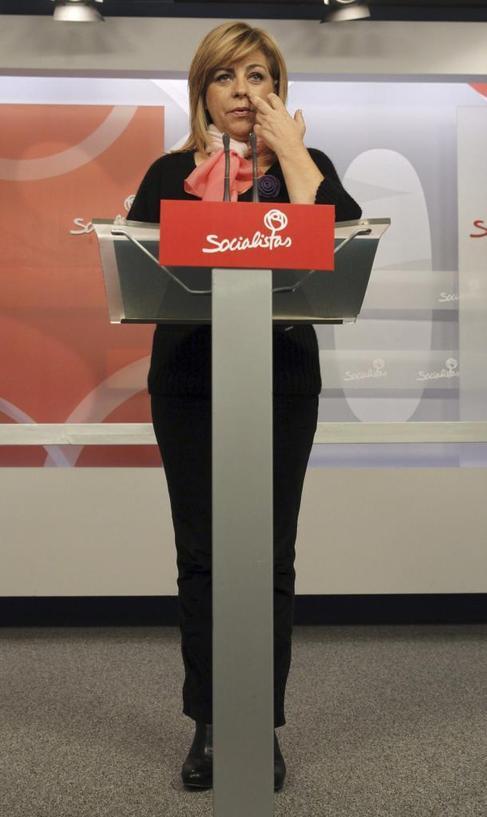 Plano total de Elena valenciano tras pupitre en la sede del PSOE.