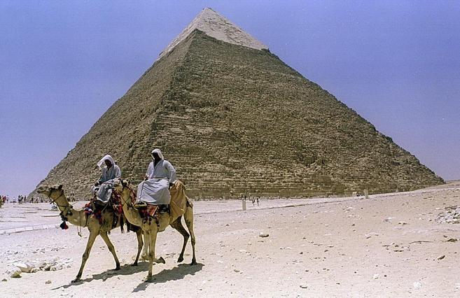 Dos egipcios en camello pasan ante la pirámide de Kefrén en Guiza,...