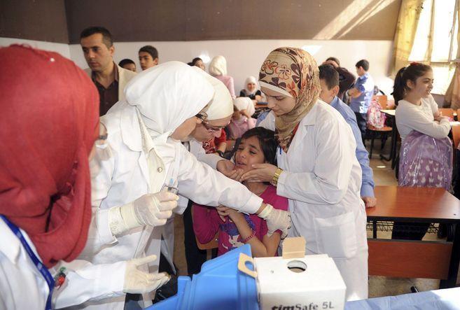 Personal sanitario vacuna a las niñas en un colegio de Damasco.