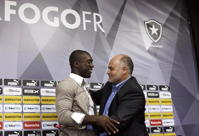 Seedorf abraza al presidente del Botafogo, Mauricio Assumpcao, en su...