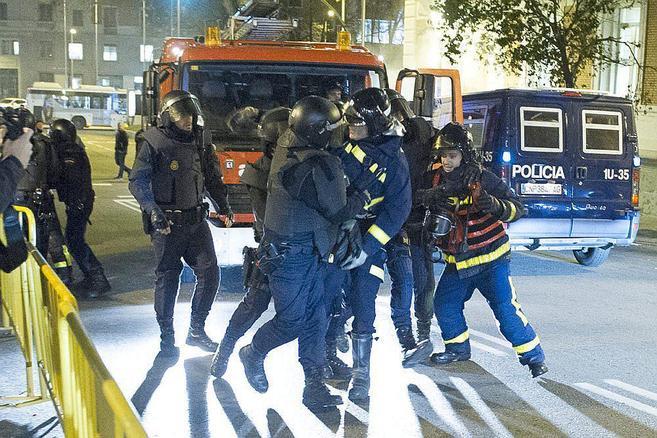 Agentes de la Policía Nacional se llevan detenido a un bombero.