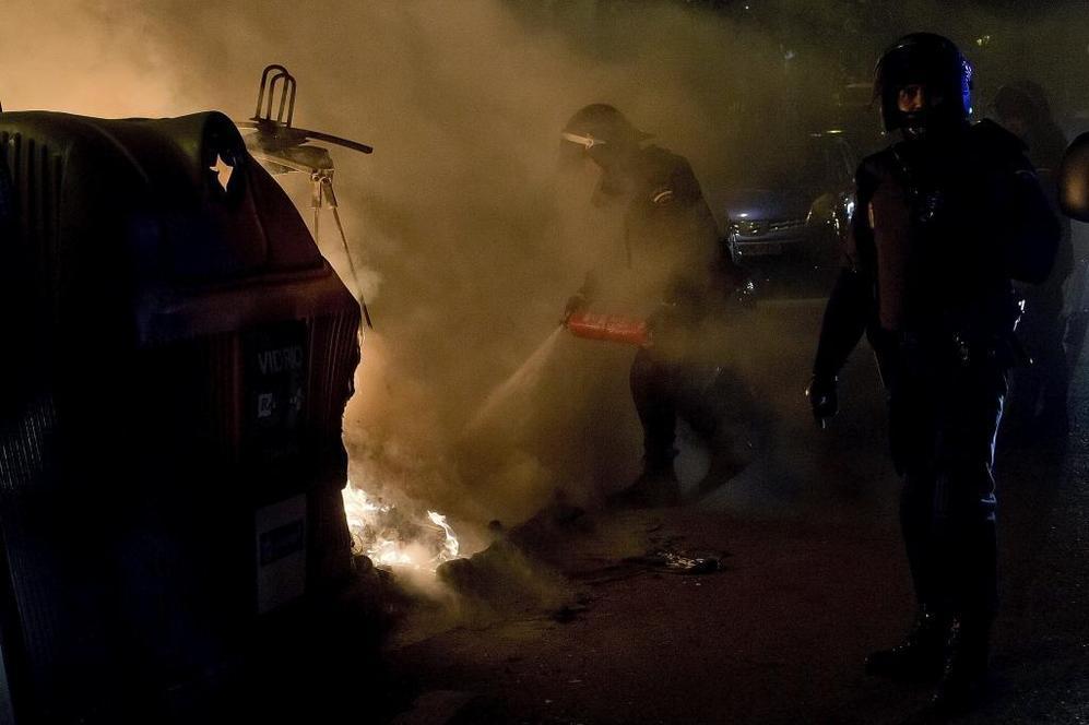 Un agente antidisturbios apaga un contenedor incendiado.