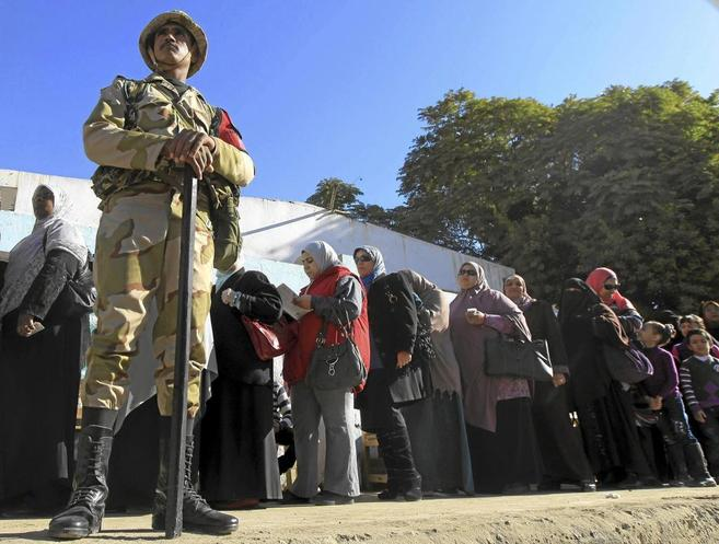 Un grupo de mujeres espera frente a un centro de votación en el...