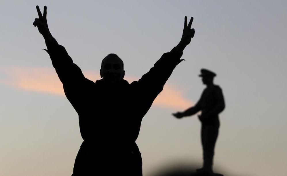 Un partidario de la Constitución hace el signo de la victoria frente...