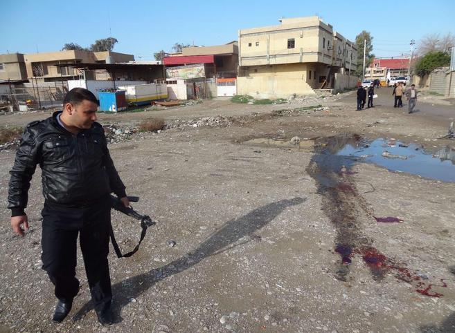 Un miembro de la seguridad iraquí observa los restos de sangre dejado...