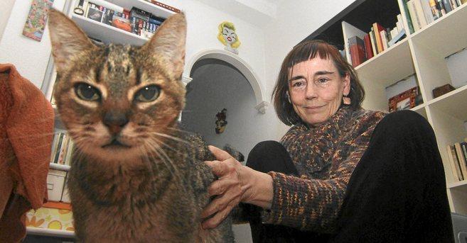 Carmen Jiménez, en su casa con uno de sus cinco gatos.