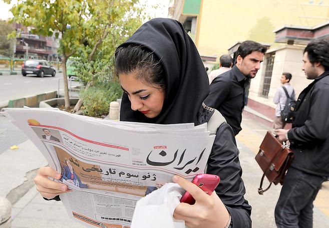 Una joven iraní lee la información sobre el acuerdo de Ginebra en...
