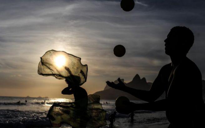 Varias personas juegan en la playa al atardecer