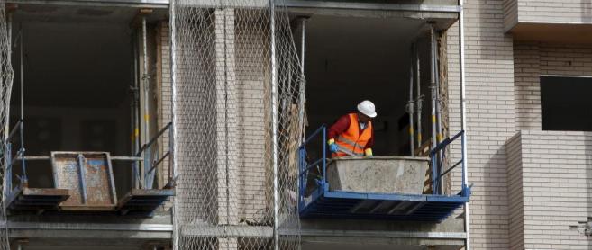 Un operario trabaja en un grupo de viviendas en construcción en...
