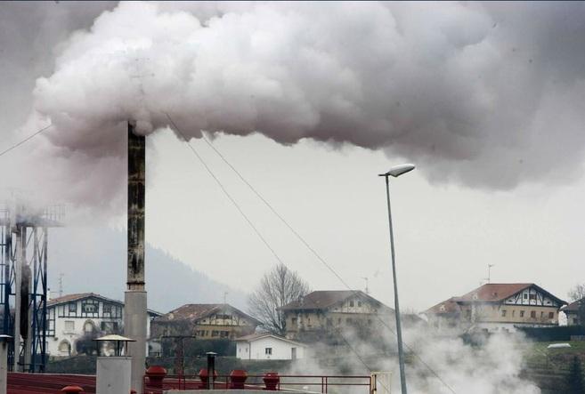 Una chimenea arroja humo en la Fábrica Maderas de Llodio.