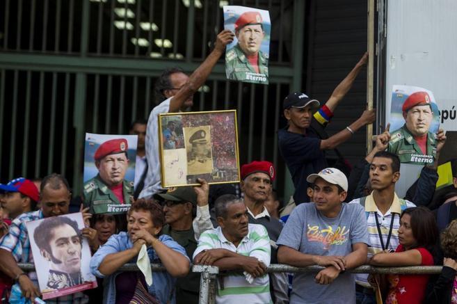 Un grupo de venezolanos espera el paso del presidente Nicolás Maduro,...