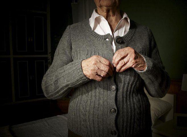 Una anciana abrochándose los botones de la chaqueta.