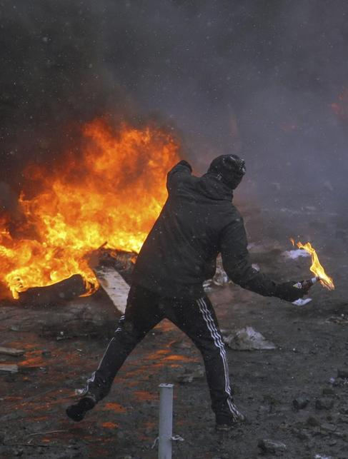 Un manifestante lanza un cóctel molotov a la policía.