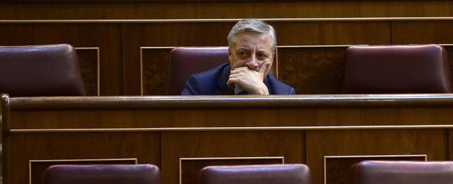 Medio Plano de José Blanco entre sillas vacías en el Congreso