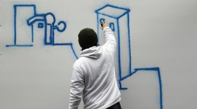 Un voluntario pinta un graffiti durante un evento artístico sobre VIH...