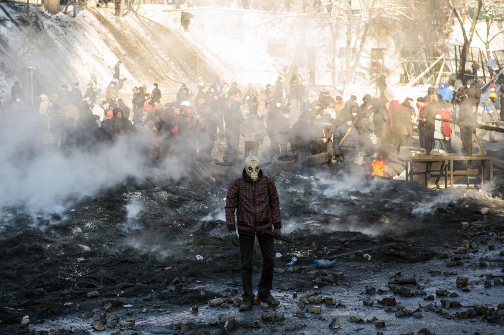 Un manifestante con una máscara antigas avanza entre las cenizas de...
