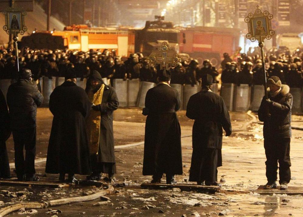 Un grupo de curas ortodoxos caminan hacia un cordón policial esta...