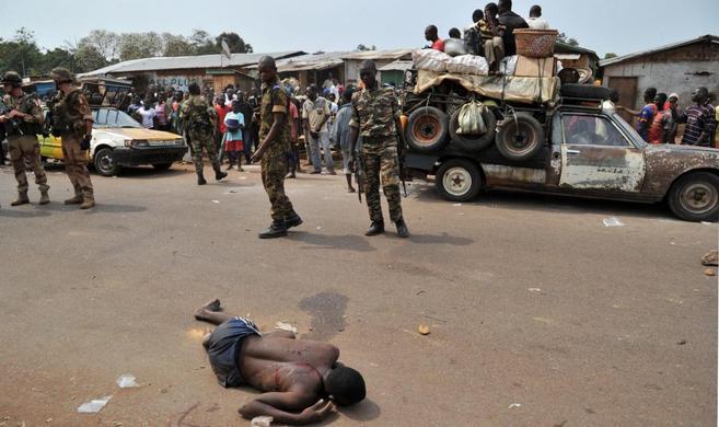 Soldados de la fuerza internacional de paz observan el cadáver de un...
