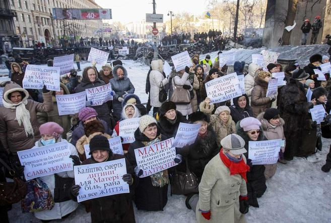 Varias mujeres muestran pancartas delante de las fuerzas policiales...