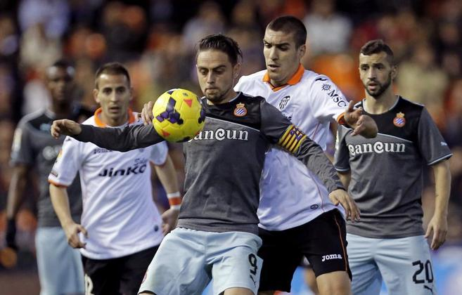 Oriol Romeu trata de arrebatarle el balón a Sergio García.