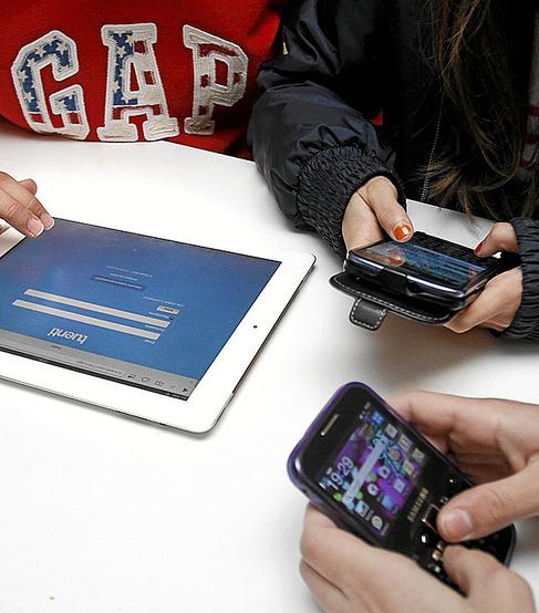 Menores con sus móviles y tabletas navegando por redes sociales.