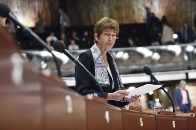 Anne Brasseur, detrás de una larga mesa con varios micrófonos, con...