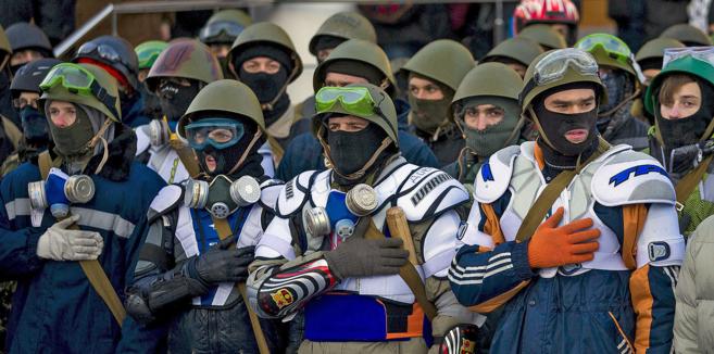 Opositores ucranianos vestidos de paramilitares cantan el himno...