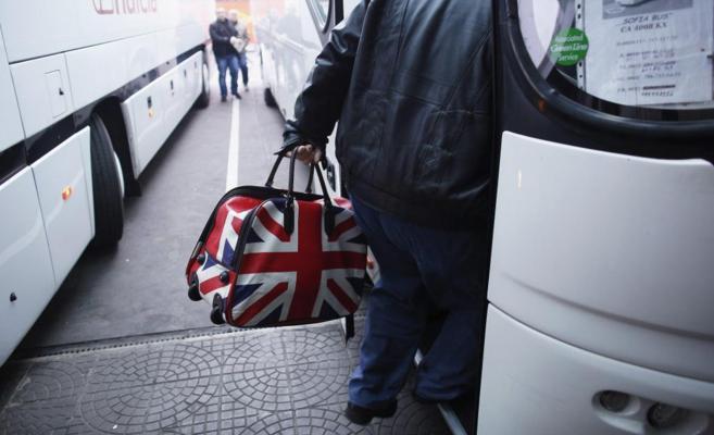 Un inmigrante sube a un autobús en la estación central de Sofía con...