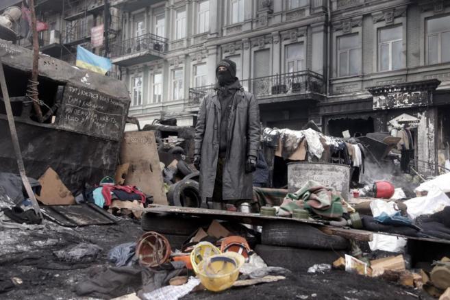 Un manifestante con una máscara antigás delante de una barricada en...
