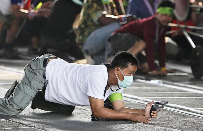 Un manifestante antigubernamental saca su arma en un enfrentamiento...