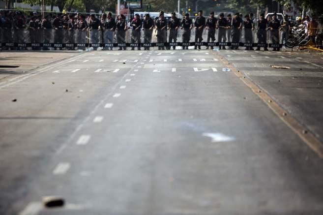 Agentes de policía forman una línea de defensa entre manifestantes...